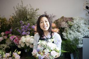 花屋で花束を持って笑っている女性の写真素材 [FYI04766114]
