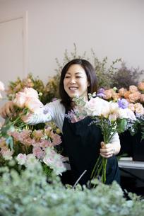 花屋で仕事をしている笑顔の女性の写真素材 [FYI04766117]