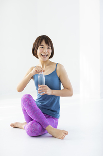 白い部屋でストレッチの合間に水分を補給する笑顔の女性の写真素材 [FYI04766365]