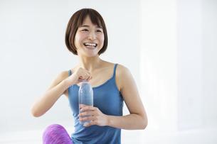 白い部屋で水分を補給する笑顔の女性の写真素材 [FYI04766369]