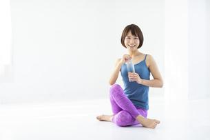 白い部屋でストレッチの合間に水を補給する笑顔の女性の写真素材 [FYI04766374]