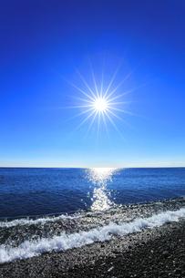 浜辺に寄せる波と空に太陽の写真素材 [FYI04766634]