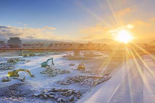 新雪の別所線千曲川橋梁復旧工事現場と朝日の写真素材 [FYI04767091]