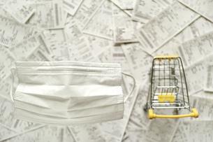 ぼけた買い物カートとレシートが背景の白い不織布マスクのクローズアップ。の写真素材 [FYI04767510]
