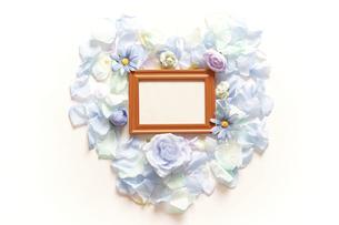 造花で模ったハートの中に横長の木製フォトフレームと白いコピースペース。平置きの俯瞰撮影。白バック。の写真素材 [FYI04767727]