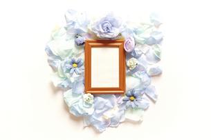造花で模ったハートの中に縦長の木製フォトフレームと白いコピースペース。平置きの俯瞰撮影。白バック。の写真素材 [FYI04767732]