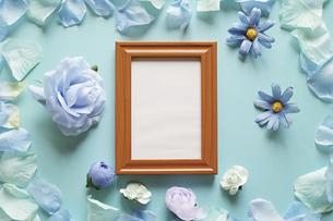 青を基調とした造花と背景。中央に縦長の木製フォトフレームの中に白いコピースペース。平置きの俯瞰撮影。の写真素材 [FYI04767746]