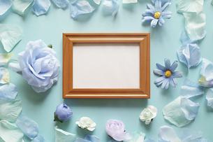 青を基調とした造花と背景。中央に横長の木製フォトフレームの中に白いコピースペース。平置きの俯瞰撮影。の写真素材 [FYI04767749]