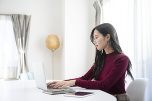 リビングでパソコン作業をする若い日本人女性の写真素材 [FYI04768023]