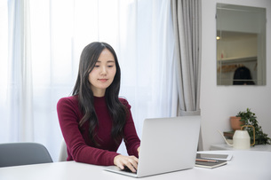 リビングでパソコン作業をする若い日本人女性の写真素材 [FYI04768024]