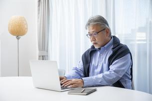 リビングでパソコン作業をするシニア男性の写真素材 [FYI04768036]