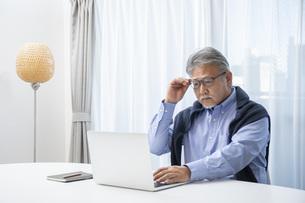 リビングでパソコン作業をするシニア男性の写真素材 [FYI04768038]