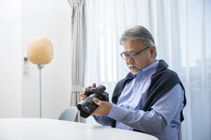 リビングでカメラを触るシニア男性の写真素材 [FYI04768039]