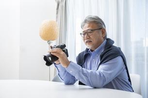 リビングでカメラを触るシニア男性の写真素材 [FYI04768040]