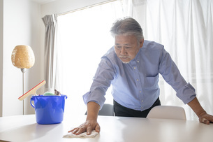リビングの掃除をするシニア男性の写真素材 [FYI04768044]