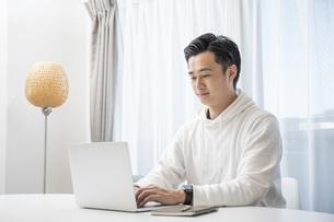 リビングでパソコン作業をする若い男性の写真素材 [FYI04768046]