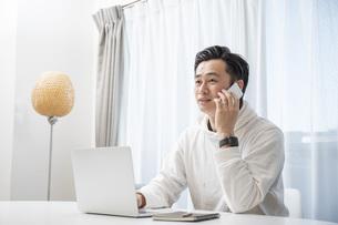 リビングでパソコン作業をする若い男性の写真素材 [FYI04768047]