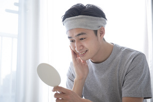 部屋でスキンケアをする若い日本人の男性の写真素材 [FYI04768049]