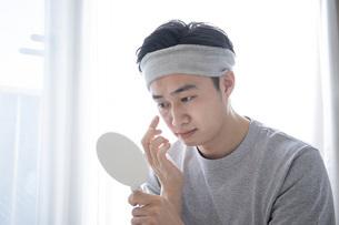 部屋でスキンケアをする若い日本人の男性の写真素材 [FYI04768050]