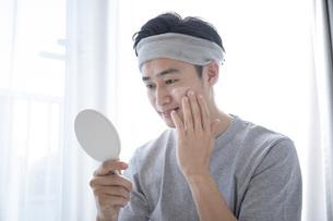 部屋でスキンケアをする若い日本人の男性の写真素材 [FYI04768052]