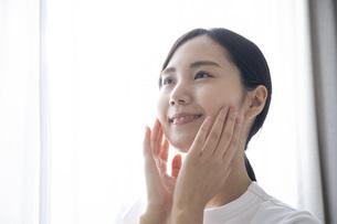 部屋でスキンケアをする若い日本人の女性の写真素材 [FYI04768055]