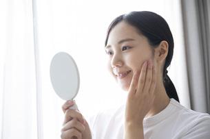 部屋でスキンケアをする若い日本人の女性の写真素材 [FYI04768056]