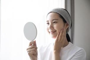 部屋でスキンケアをする若い日本人の女性の写真素材 [FYI04768057]