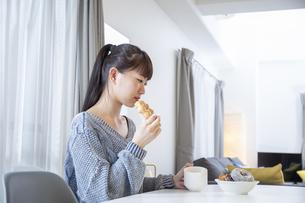 リビングでドーナツを食べる日本人女性の写真素材 [FYI04768070]