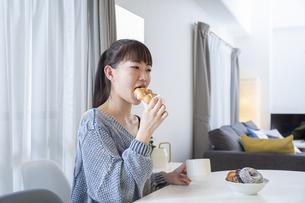 リビングでドーナツを食べる日本人女性の写真素材 [FYI04768071]