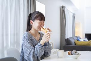 リビングでドーナツを食べる日本人女性の写真素材 [FYI04768072]