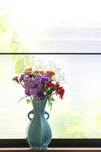 青色の花瓶にいけた様々な花のブーケの写真素材 [FYI04768540]
