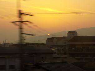 電車の窓から見える日常と沈む夕日の写真素材 [FYI04768897]