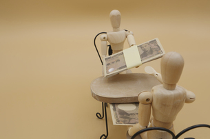 机の下でキックバックを受け取るデッサン人形の写真素材 [FYI04769367]