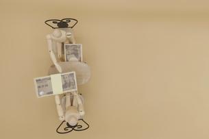 机の下でキックバックを受け取るデッサン人形の写真素材 [FYI04769370]