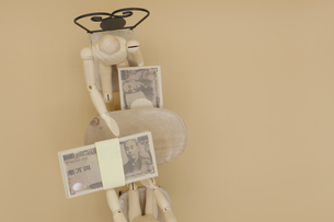 机の下でキックバックを受け取るデッサン人形の写真素材 [FYI04769371]