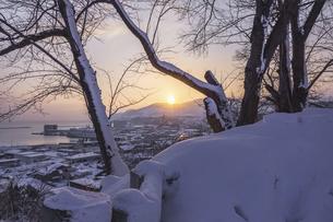 雪の丘から見る日の出の写真素材 [FYI04769410]