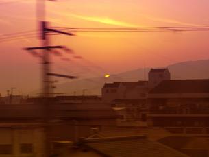 電車の窓から見える日常と沈む夕日の写真素材 [FYI04769455]