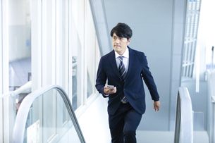 エスカーレーターを登るビジネスマンの写真素材 [FYI04769673]