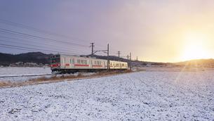 五加のカーブを走る別所線の1000系電車と朝日の写真素材 [FYI04769936]