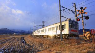 下之郷を走る夕日に輝く別所線の1000系電車の写真素材 [FYI04769950]