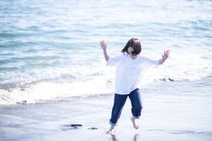 海辺ではしゃぐ女性の写真素材 [FYI04770186]