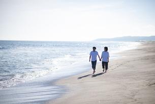 海辺で手をつなぐカップルの写真素材 [FYI04770195]