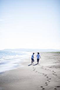 浜辺を走るカップルの写真素材 [FYI04770204]