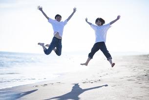 浜辺でジャンプをするカップルの写真素材 [FYI04770205]