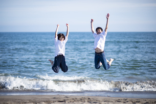 浜辺でジャンプをするカップルの写真素材 [FYI04770209]