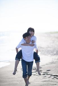 浜辺で恋人を背負う男性の写真素材 [FYI04770210]