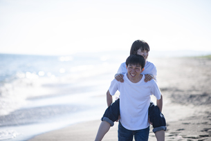 浜辺で恋人を背負う男性の写真素材 [FYI04770211]