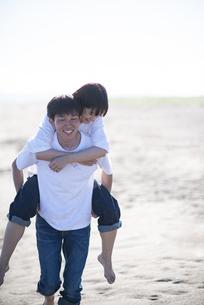 浜辺で恋人を背負う男性の写真素材 [FYI04770212]
