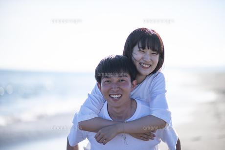 浜辺で恋人を背負う男性の写真素材 [FYI04770214]