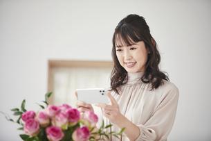 花をスマートフォンで撮影する女性の写真素材 [FYI04770217]